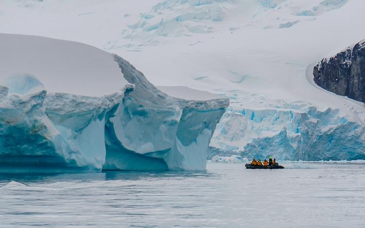 zodiac cruising by a glacier in antarctica